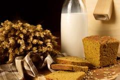 Stilleben med en glass tillbringare av mjölkar, rågbröd, öron av havre Royaltyfria Bilder