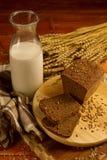 Stilleben med en glass tillbringare av mjölkar, rågbröd, öron av havre Royaltyfri Fotografi