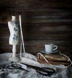 Stilleben med en kopp kaffe, sax, skyltdockasömnad och snör åt på en bakgrund av grova träväggar Tappning arkivbild