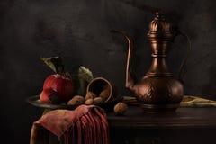Stilleben med en koppartillbringare, äpplen och muttrar arkivbilder