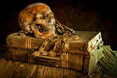 Stilleben med en mänsklig skalle med den gammal skattbröstkorgen och guld, arkivfoton