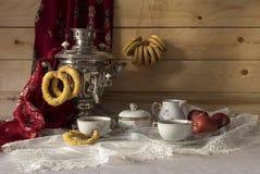Stilleben med en samovar, baglar och te Royaltyfria Bilder