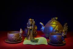 Stilleben med en statyett av guden av te Arkivfoto