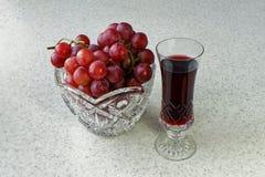 Stilleben med ett exponeringsglas av vin och en kristallvas med druvor fotografering för bildbyråer