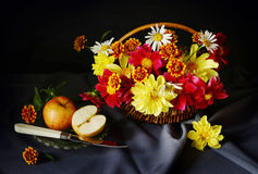 Stilleben med ett snittäpple och härliga blommor i korgen Fotografering för Bildbyråer