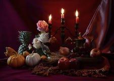Stilleben med frukter förlades samman med ljusstaken Arkivbilder
