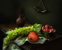 Stilleben med granatäpplen, druvor och kannan arkivfoto