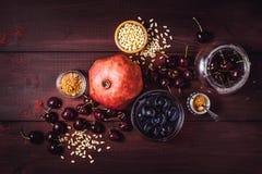 Stilleben med granatäpplet, körsbäret och kryddor på den röda trätabellen Begrepp av den bästa sikten för orientaliska frukter arkivbild