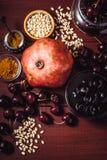 Stilleben med granatäpplet, körsbäret och kryddor på den röda trätabellen Begrepp av vertikala orientaliska frukter royaltyfri bild