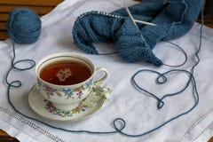 Stilleben med handarbete och kopp te på den gamla doyleyen royaltyfria bilder