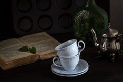 Stilleben med koppar och boken i tappning utformar Royaltyfri Foto