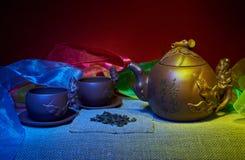 Stilleben med koppar, tefat, en teinfuser av handgjord lera Royaltyfri Foto