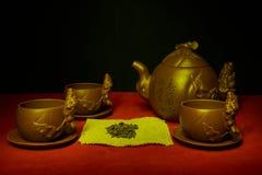 Stilleben med koppar, tefat, en teinfuser av handgjord lera Arkivfoton