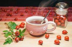 Stilleben med koppen av nytt te och rosa höfter på trätabellen Arkivfoton