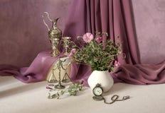 Stilleben med lösa blommor och en klocka Arkivfoto