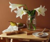 Stilleben med liljablommabuketten och päron Arkivfoto