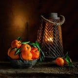 Stilleben med mandariner i den tenn- bunken och levande ljuset på träbakgrund Royaltyfri Bild