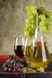Stilleben med mogna druvor, vinexponeringsglas och vinflaskor i gammal källare arkivbilder