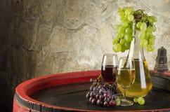 Stilleben med mogna druvor, vinexponeringsglas och vinflaskor i gammalt royaltyfria foton
