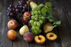 Stilleben med nya frukter i en korg på tabellen Arkivfoton