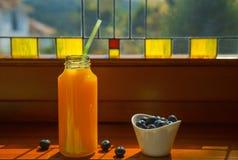 Stilleben med orange fruktsaft för sunda frukostingredienser i glasflaska och vitbunken med blåbär står vid det färgrikt fotografering för bildbyråer