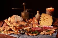 Stilleben med ost, stearinljuset, italiensk salami, olika typer av bröd, oliv, etc. royaltyfri foto