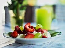 Stilleben med plattan med jordgubbar, druvor och icecream Royaltyfri Fotografi