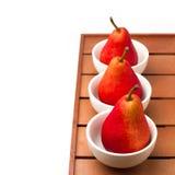 Stilleben med röda pears och vita bunkar Royaltyfri Bild