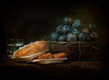 Stilleben med sött bröd och mogna plommoner Arkivbilder