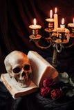 Stilleben med skallen, boken och ljusstaken Arkivfoton