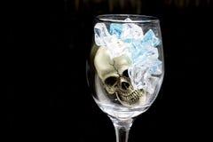 Stilleben med skallen i ett exponeringsglas av vin med blå is Arkivbild