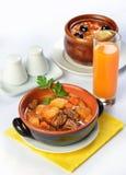 Stilleben med soppa och kött i keramiska krukor Arkivbild