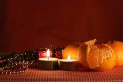 Stilleben med stearinljuset och mandarinesna. royaltyfri bild