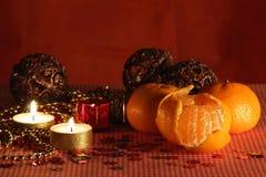 Stilleben med stearinljuset och mandarinesna. arkivbild