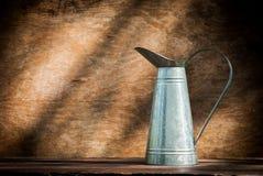Stilleben med tillbringaren som göras av zink Arkivfoton