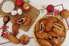 Stilleben med traditionella ryska pajer, ingredienser - mjöl, ägg, äpplen På autentisk bordduk med en träsked med PA royaltyfri fotografi