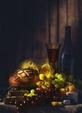 Stilleben med vin, druvor, bröd och olika slag av ost royaltyfri fotografi