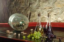 Stilleben med vinexponeringsglas, vinflaskor och druvor i gammal källare arkivfoto