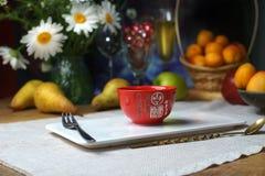 Stilleben med vita tusenskönor, päron, aprikors, persikor, i mitten på en porslinställning per den röda koppen för te med hierogl arkivfoton