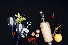 Stilleben med vitt vin i glasflaska på svart bakgrund Exponeringsglas av vin med nya druvor Flaska och footed exponeringsglas Fr Royaltyfria Bilder