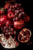 Stilleben på en mörk bakgrund Exponeringsglas för vin (starksprit), frukter a royaltyfri foto