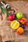 Stilleben på säckvävbakgrund: äpple persikor, orance, plommon Royaltyfri Bild