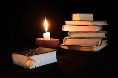 Stilleben på svart bakgrund, staplade böcker, stearinljus, en bok på Royaltyfri Bild