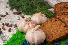 Stilleben på träbakgrund: bröd vitlök, fänkål, bayberry Royaltyfri Fotografi