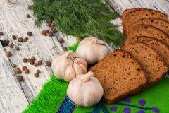 Stilleben på träbakgrund: bröd vitlök, fänkål, peppar Royaltyfria Foton