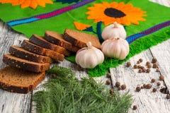 Stilleben på träbakgrund: svart bröd, vitlök, fänkål, lodisar Royaltyfri Bild