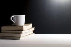 Stilleben - pålagda gamla böcker för en kopp kaffe Fotografering för Bildbyråer