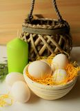 Stilleben - påskgarnering - ägg i en korg med en korglampa och en grön dekorativ stearinljus Royaltyfria Foton