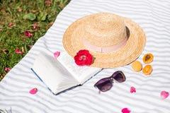 Stilleben, Straw Hat och bok på skyla och kvinnasolglasögon royaltyfri bild