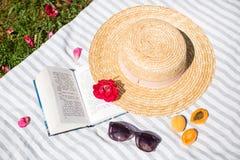 Stilleben, Straw Hat och bok på skyla och kvinnasolglasögon arkivfoton